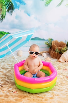Heureux petit garçon se baigne dans une piscine gonflable lumineuse sur une plage de sable avec des palmiers au bord de la mer