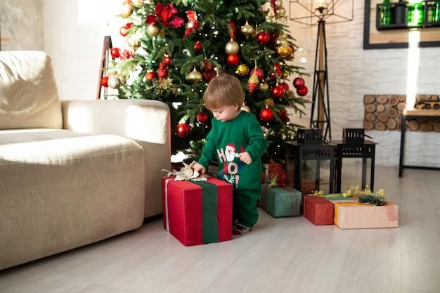 Heureux petit garçon souriant jouant avec des coffrets cadeaux de noël