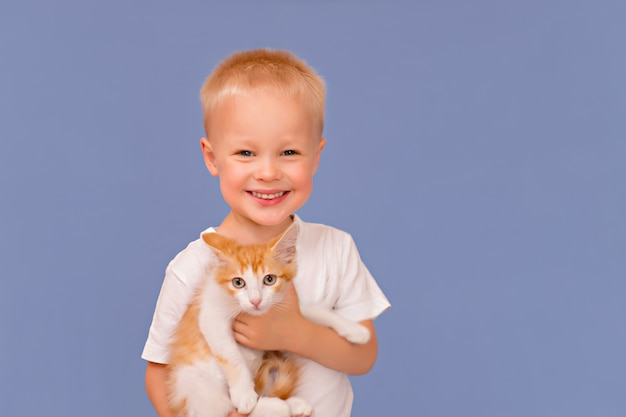 Heureux petit garçon avec un sourire tient dans ses mains un petit chaton au gingembre sur fond bleu