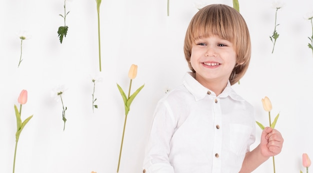 Heureux petit garçon tenant la tulipe