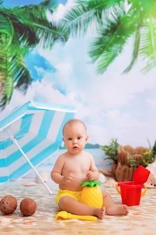 Heureux petit garçon en train de bronzer sur une plage de sable au bord de la mer avec des palmiers sous un parasol