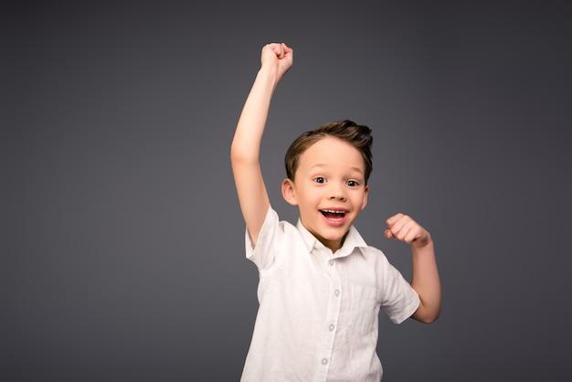 Heureux petit garçon triomphant avec les mains levées