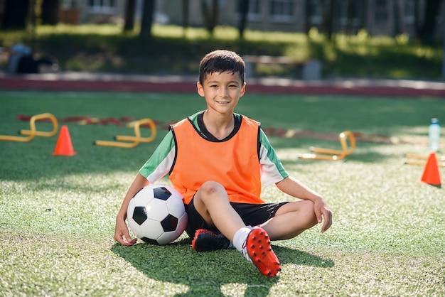 Heureux petit garçon en uniforme assis sur un terrain de football avec un ballon