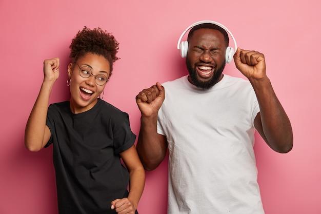 Heureux petite amie ethnique et petit ami apprécient la musique dans les écouteurs, dansent joyeusement, serrent les poings, vêtus de t-shirts décontractés, rient joyeusement, isolés sur le mur rose.