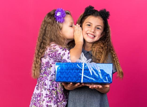 Heureux petite fille chuchote à l'oreille de sourire petite fille caucasienne tenant une boîte-cadeau isolée sur un mur rose avec espace de copie
