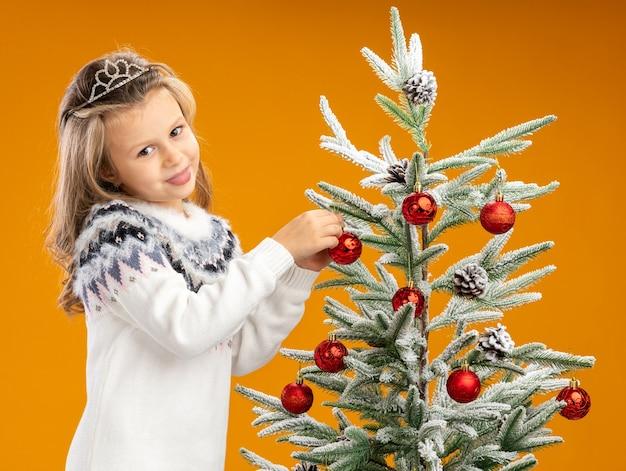 Heureux petite fille debout à proximité de l'arbre de noël portant diadème avec guirlande sur le cou accroche jouet sur l'arbre isolé sur fond orange