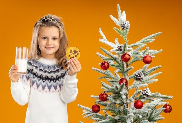 Heureux petite fille debout à proximité de l'arbre de noël portant diadème avec guirlande sur le cou tenant un verre de lait avec des biscuits isolé sur fond orange