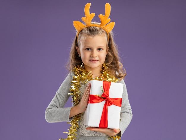 Heureux petite fille portant un cerceau de cheveux de noël avec guirlande sur le cou tenant la boîte-cadeau isolé sur fond bleu