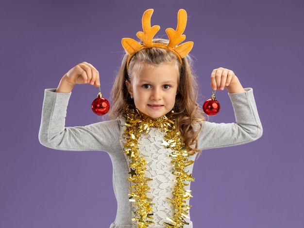 Heureux petite fille portant un cerceau de cheveux de noël avec guirlande sur le cou tenant des boules de noël isolé sur fond bleu