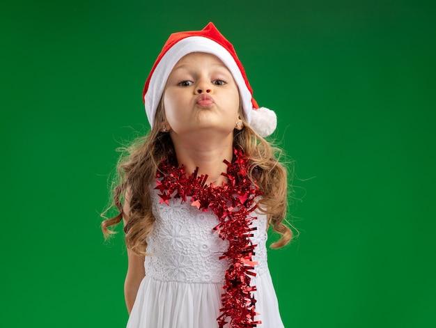 Heureux petite fille portant un chapeau de noël avec guirlande sur le cou montrant le geste de baiser isolé sur fond vert
