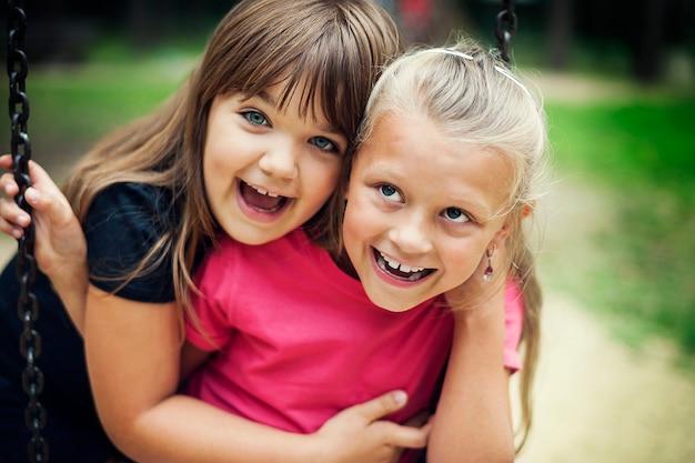 Heureux petites filles se balançant dans un parc