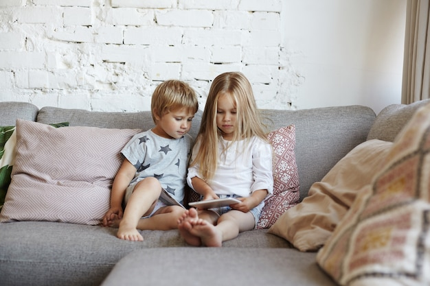 Heureux petits enfants sont assis dans le salon