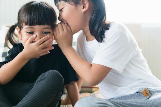 Heureux petits frères et sœurs asiatiques partageant des secrets