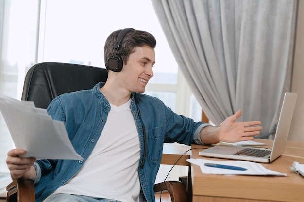 Heureux pigiste avec des écouteurs ayant une conférence téléphonique au bureau à domicile