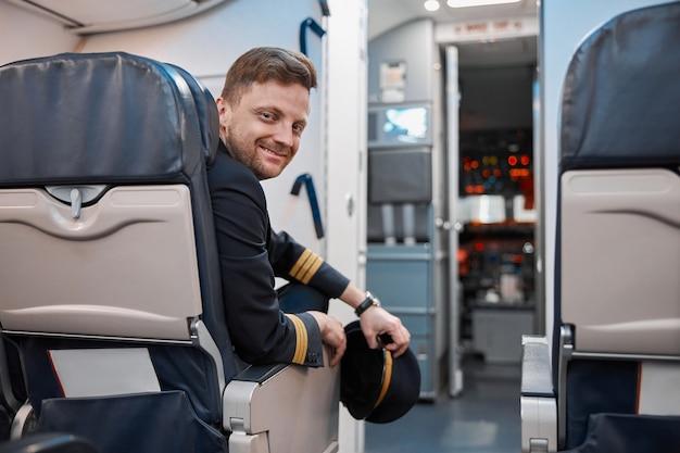 Heureux pilote caucasien confiant dans le salon de l'avion
