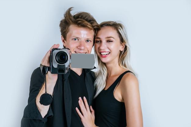 Heureux portrait d'un couple tenant une caméra vidéo et enregistrer un clip vidéo