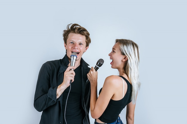 Heureux portrait d'un couple tenant un micro et chanter une chanson