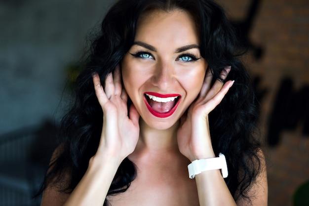 Heureux portrait émotionnel d'une femme brune heureuse souriant et riant, yeux bleus et maquillage lumineux.