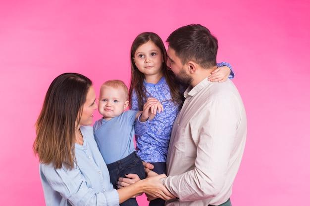 Heureux portrait de famille métisse souriant sur mur rose