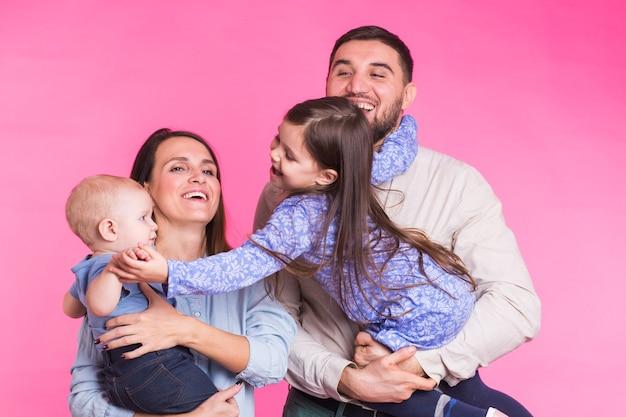 Heureux portrait de famille métisse souriant sur rose
