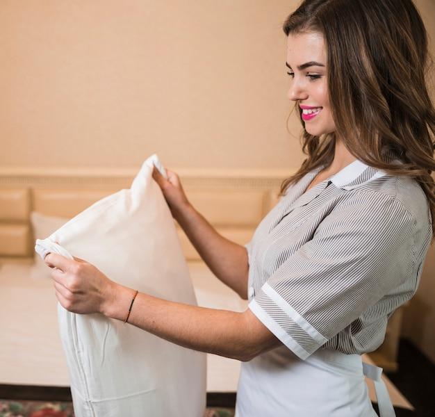Heureux portrait d'une femme de chambre ajustant l'oreiller blanc