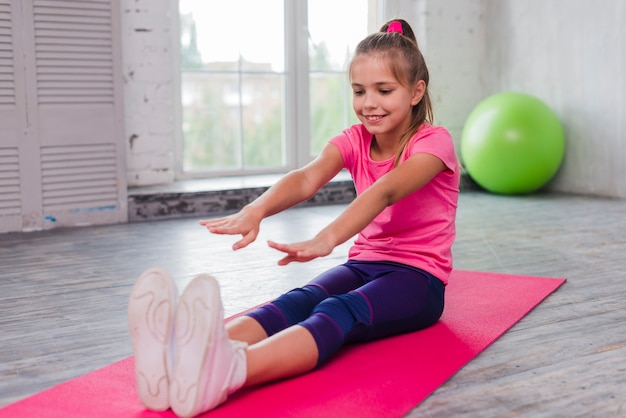 Heureux portrait d'une fille assise sur un tapis d'exercice qui s'étend ses mains