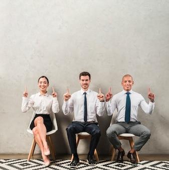 Heureux portrait d'un jeune homme d'affaires et femme d'affaires assis sur une chaise, pointant leurs doigts vers le haut