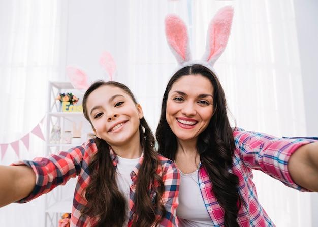Heureux portrait de mère et fille prenant selfie le jour de pâques