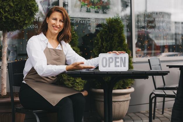 L'heureux propriétaire d'un café dans un tablier tient un panneau ouvert près du café et regarde la caméra. serveuse.