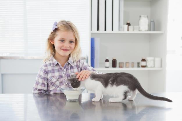 Heureux propriétaire caresser son chat boire du lait