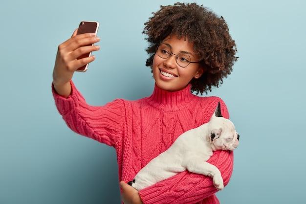 Heureux propriétaire de chien incline la tête, a une coiffure afro, vêtu d'un pull rose, tient un petit chiot endormi