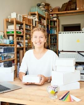 Heureux propriétaire d'entreprise locale. femme entrepreneur ramassant et emballant des cadeaux pour les clients pour noël. businesswoman mettant des produits dans des boîtes pour l'envoi au client