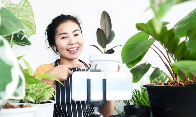 Heureux propriétaire de magasin asiatique vendant des plantes en ligne avec l'appareil photo