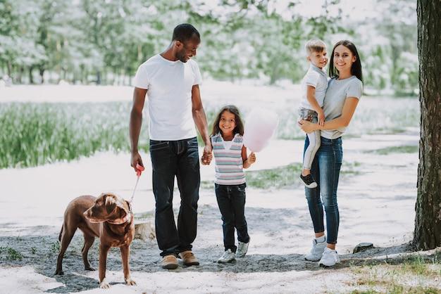 Heureux propriétaires d'animaux jeune famille marchant avec un chien