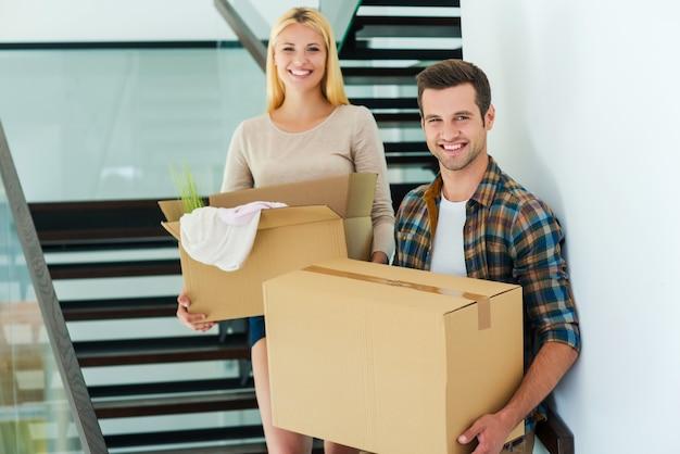 Heureux propriétaires de maison neuve. joyeux jeune couple tenant des boîtes en carton tout en se tenant dans les escaliers de leur nouvelle maison