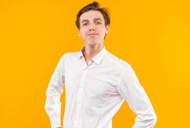 Heureux à la recherche d'appareil photo jeune beau mec vêtu d'une chemise blanche mettant les mains sur la hanche isolé sur le mur orange