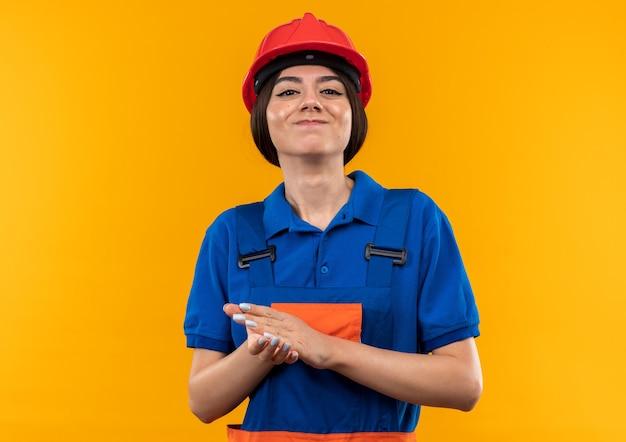 Heureux de regarder la caméra jeune femme de constructeur en uniforme, main dans la main