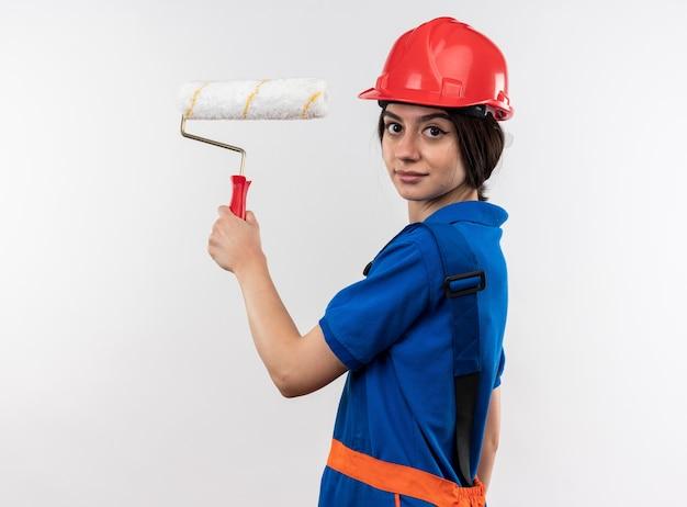 Heureux de regarder la caméra jeune femme de constructeur en uniforme tenant une brosse à rouleau