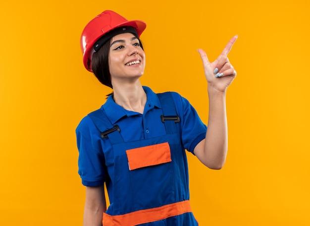 Heureux de regarder côté jeune constructeur femme en uniforme points à côté