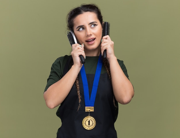 Heureux de regarder côté jeune femme barbier en uniforme et médaille tenant des peignes autour des oreilles isolées sur un mur vert olive