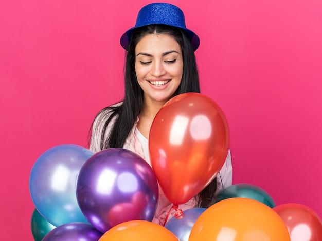 Heureux de regarder vers le bas belle jeune fille portant un chapeau de fête debout derrière des ballons