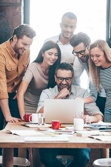 Heureux des résultats de leur travail. groupe de six jeunes gens d'affaires joyeux regardant un ordinateur portable et souriant tout en regardant un ordinateur portable ensemble