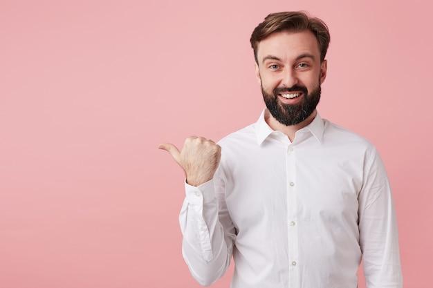 Heureux séduisant jeune homme brune avec une barbe luxuriante portant une chemise blanche tout en posant sur un mur rose, montrant ses émotions agréables et pointant de côté avec le pouce