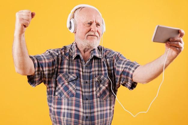 Heureux senior danser et regarder de la musique vidéo