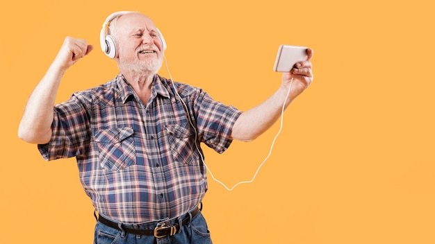 Heureux senior en regardant des vidéos de musique sur le téléphone