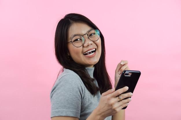 Heureux avec smartphone belle femme asiatique portant une chemise à col roulé grise isolée sur rose