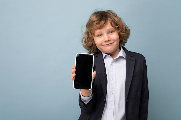 Heureux souriant beau garçon positif avec des cheveux blonds bouclés portant un costume tenant un téléphone isolé sur
