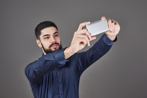 Heureux souriant beau jeune homme barbu faisant selfie.