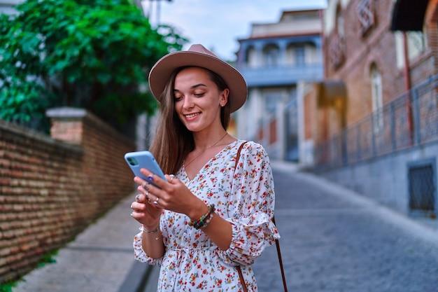 Heureux souriant beau voyageur joyeux mignon jeune fille utilisant un smartphone pendant le week-end de vacances tout en visitant