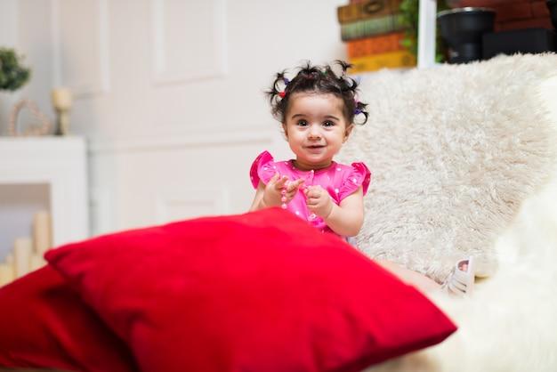 Heureux souriant bébé douce fille assise sur le canapé avec ourson
